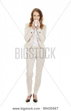 Business woman drinking coffee from cup.