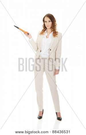 Attractive businesswoman pointing aside with oversized pen.