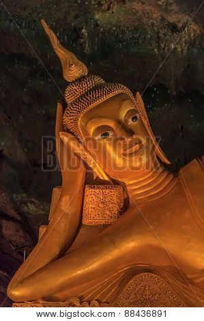 Head Of The Statue Of Reclining Buddha In A Cave Temple In Thailand