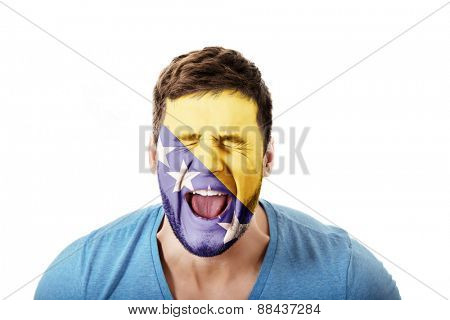 Screaming man with Bosnia and Herzegovina flag painted on face.