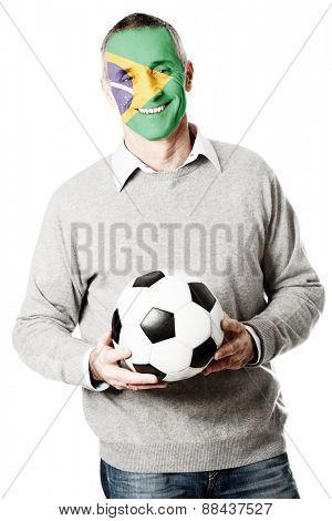 Mature man with Brazil flag painted on face.