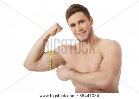 Handsome muscular man measuring his biceps.