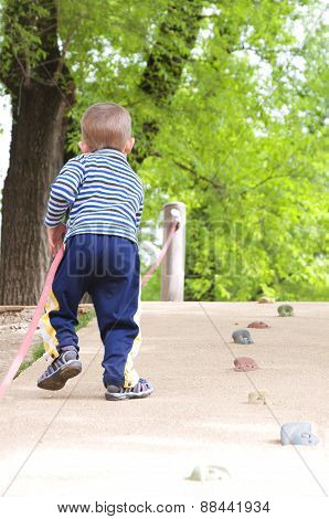 child climbs up the wall in the park