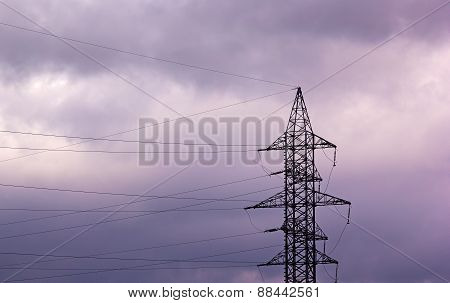 High Voltage Power Pylon On A Cloudy Sky At Sunset