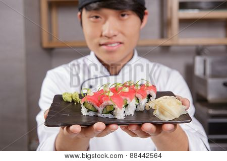 Cook stretches out a plate with sushi