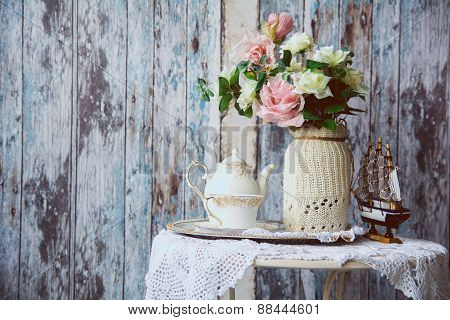 Porcelain Teapot And Cup On A Table With A Vase With Artificial Flowers On A Background Of The Old W