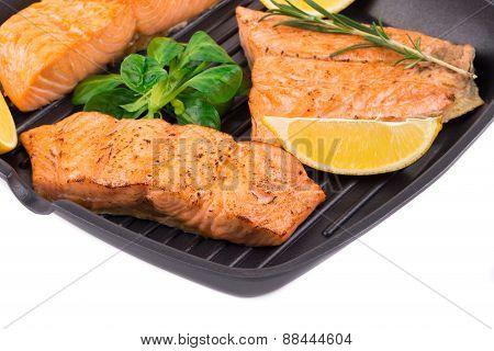 Fried salmon fillet in pan with lemon.