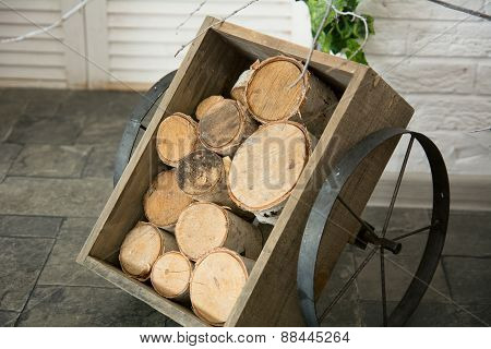 Birch Logs In A Wooden Cart With Iron Wheels