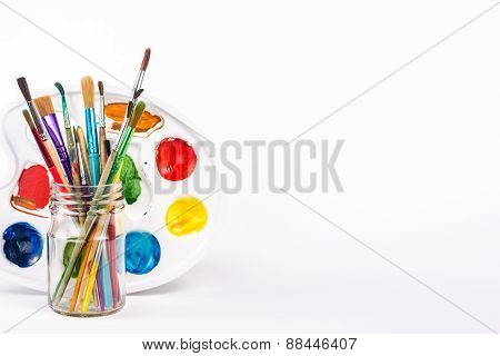 isolated paints palette and paints brushes in a glass