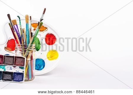 paints palette and paints brushes in glass