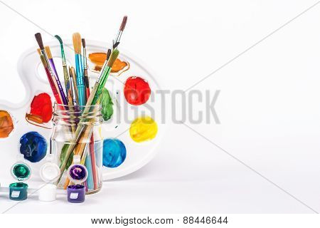 isolated water paint and paints brushes in a glass