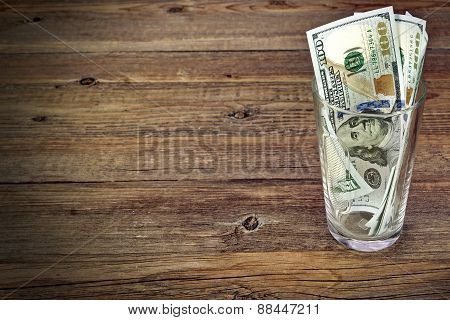 Glass  With Money  For Big Tip With Dollar Bills