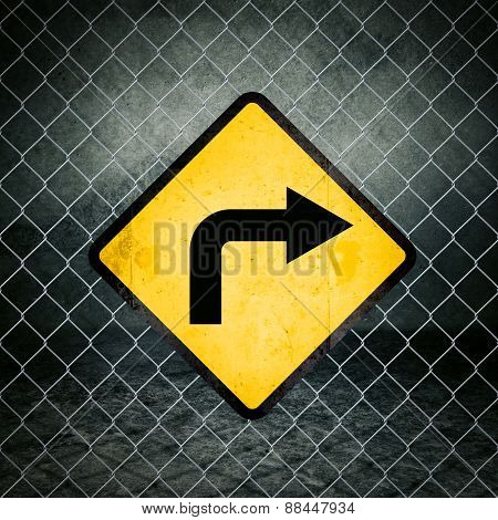 Right Direction Grunge Yellow Warning Sign On Chainlink Fence