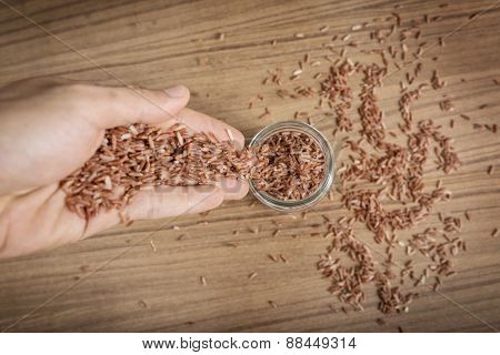 Brown Rice In Hand On Wooden Background