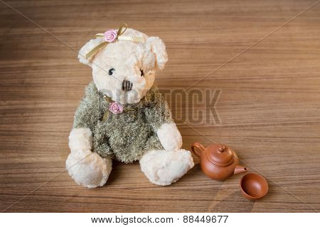 Toy Teddy Bear And Tea Kettle And Cup On Wooden Background