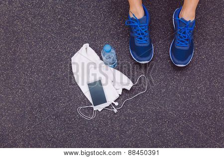 Man legs with sneakers, towel, water and smartphone in gym floor