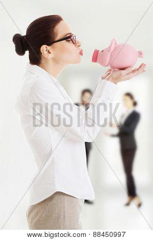 Happy businesswoman kissing a piggybank.
