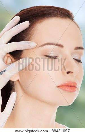 Beautiful woman gets injection before facial plastic surgery.