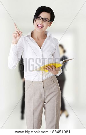 Confident businesswoman with notepad pointing up.