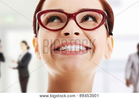 Woman with toothy smile looking up.
