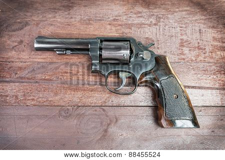 Black Revolver Gun With Bullets Isolated On Wooden Background