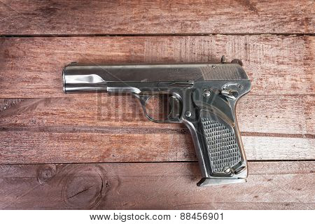 Semi-automatic 9Mm Gun Isolated On Wooden Background
