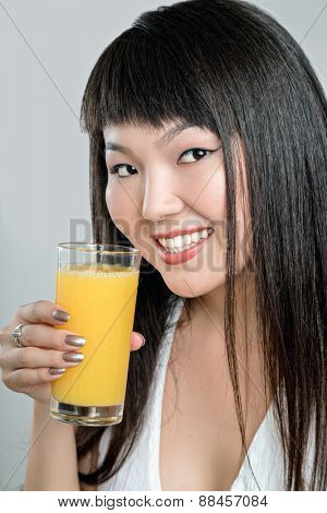 pretty asian woman drinking orange juice