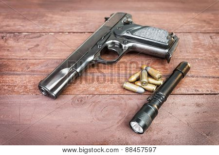 Semi-automatic 9Mm Gun And And Tactical Flashlight Lying Over On Wooden Background