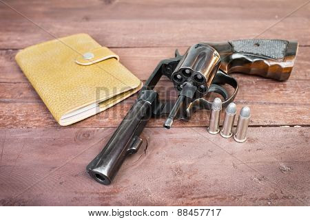 Black Revolver Gun And And Leather Bag Over On Wooden Background