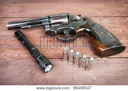 Black Revolver Gun And And Tactical Flashlight Lying Over On Wooden Background