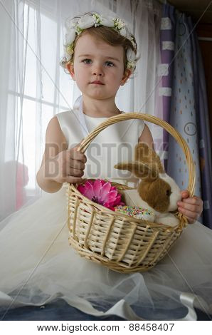 Little beautiful girl in a white dress with a rabbit in a basket