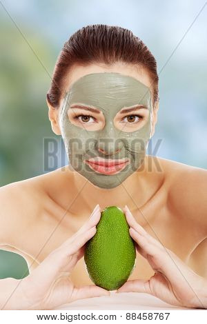 Beautiful woman in clay facial mask with avocado.