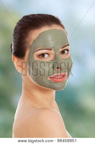 Beautiful woman with clay facial mask.