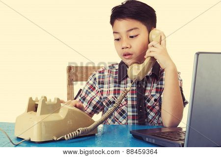 Little Asian Boy Holding Old Telephone Receiver.