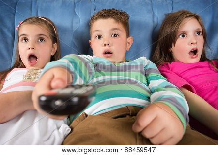 Surprised children watching TV at home
