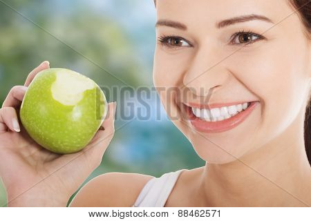 Young woman holding an apple and smiling.