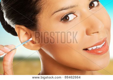 Woman cleaning ear using cotton stick.