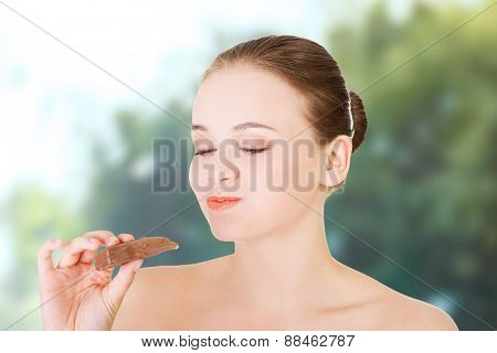 Beautiful young woman eating a chocolate bar.