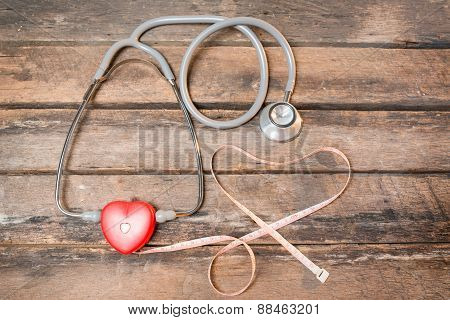Red Heart Measuring With Stethoscope And Red Pills Isolated On Wooden Background.