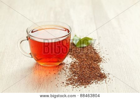 Glass cup of healthy natural herbal rooibos tea on wooden table