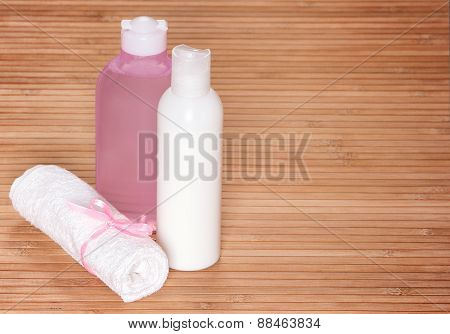 Cleansing Face Tonic And Milk With A Towel On Wooden Surface