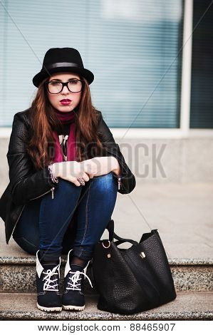 The Stylish Sad Urban Girl In Sunglasses Sits On Steps