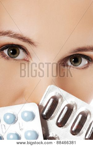 Close up woman holding pills.