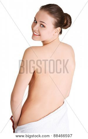Woman wrapped in towel turning back to the camera.