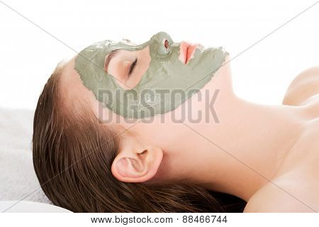 Woman getting clay mask on her face.
