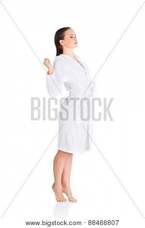 Side view woman standing, wearing bathrobe.