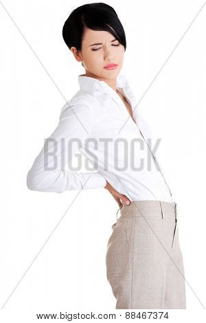 Attractive businesswoman suffers from back pain.
