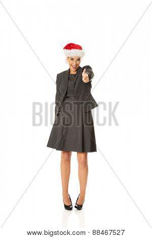 Happy businesswoman wearing christmas hat.
