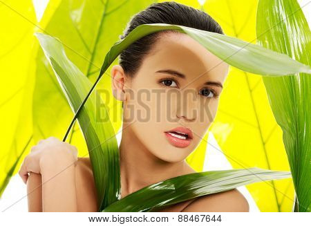 Portrait of nude woman with green leaves.