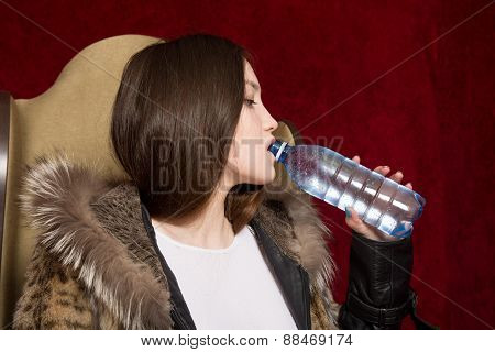 The Girl In A Fur Jacket Drinking Water From A Bottle